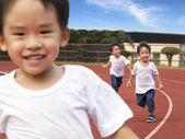 Happy kids running on the Stadium track — Stock Photo