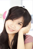 Smiling asian young girl listening to music — Stock Photo