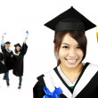 Young smiling graduate asian girl and happy students group — Stock Photo #7144769