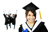 Young smiling graduate asian girl and happy students group — Stock Photo