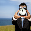 Man holding clock and cover his face — Stock Photo