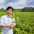 Chinese farmer holding sapling and standing on his farm — Stock Photo