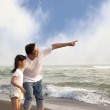 Father pointing and little girl looking it on the beach — Stock Photo #7385611