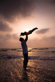 The silhouette of happy family on the beach — Stock Photo