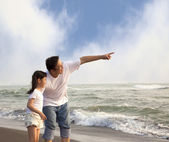 Father pointing and little girl looking it on the beach — Stock Photo