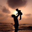 Silhouette of happy father and little girl on the beach — Stock Photo