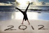 Gelukkig nieuw jaar 2012 op het strand met zonsopgang — Stockfoto