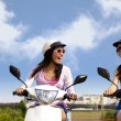 Happy girls having road trip on a scooter — Stock Photo