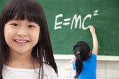 Happy girls by chalkboard with e=mc2 — Stock Photo