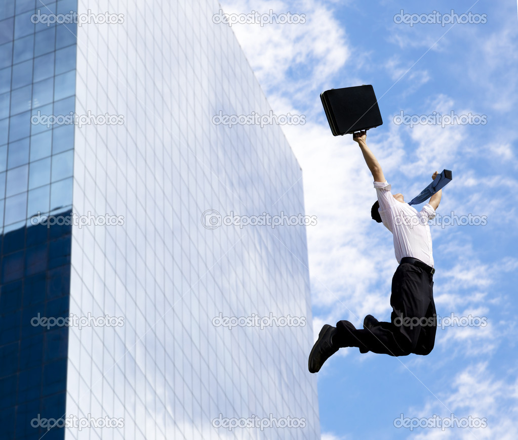Happy businessman jumping in front of a building — Stock Photo #7856318