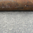 Industrial rusty steel pipe laying on pavement -  