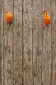 2 deflated orange balloons on worn grungy wood panel — Stock Photo