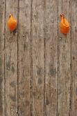 2 deflated orange balloons on worn grungy wood panel — ストック写真