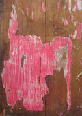 Remains pink poster grunge on piece of wood timber — Stock Photo