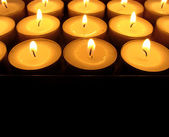 Close view of multiple candle lights on black — Stock Photo
