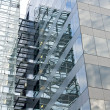 Glass facade building detail reflecting sky. - Stock Photo