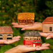 Four different houses in human hands — Stock Photo