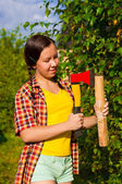 Young woman holding an axe and chock — Stock Photo