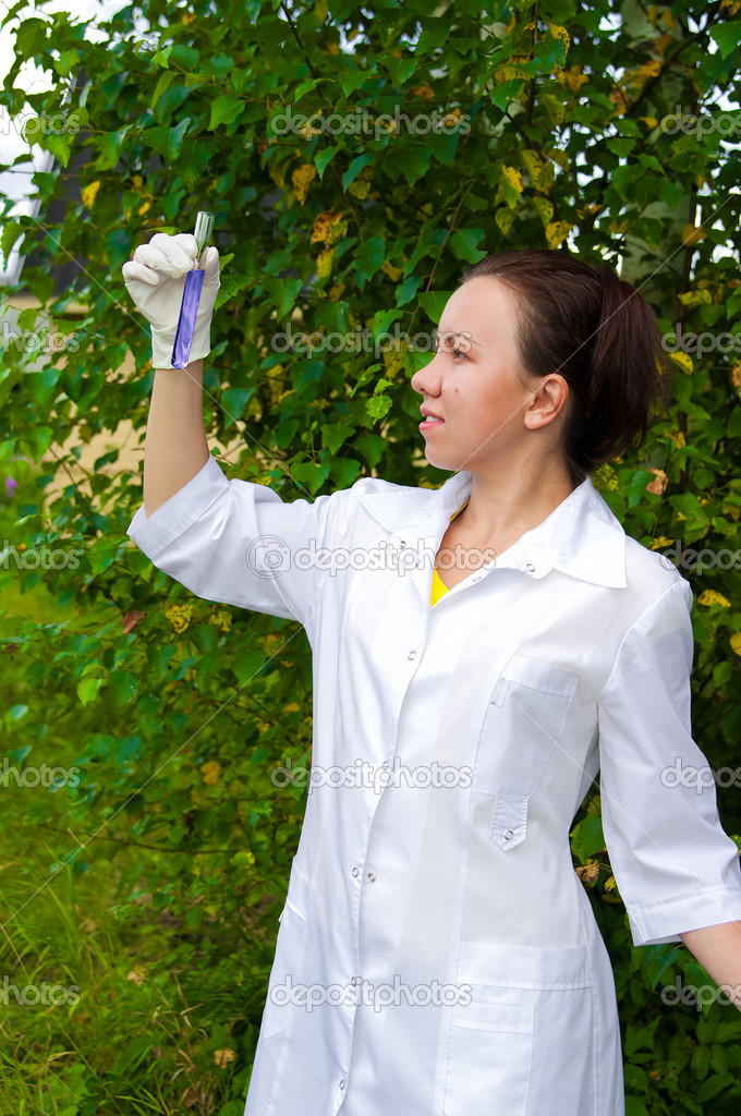 Young doctor analyzing blue liquid in test tube outdoors — Stock Photo #6806079
