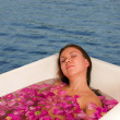 Stock Photo: Beautiful woman enjoying floral bath