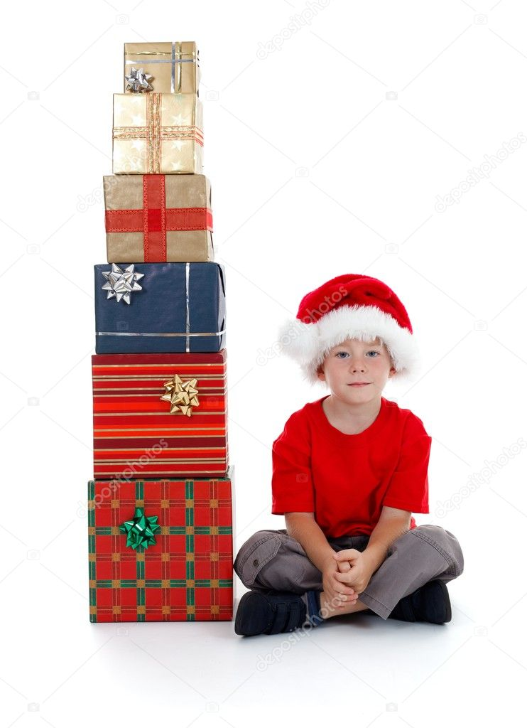 Serious child with Santa hat sitting beside stack of gifts — Stock Photo #7026131