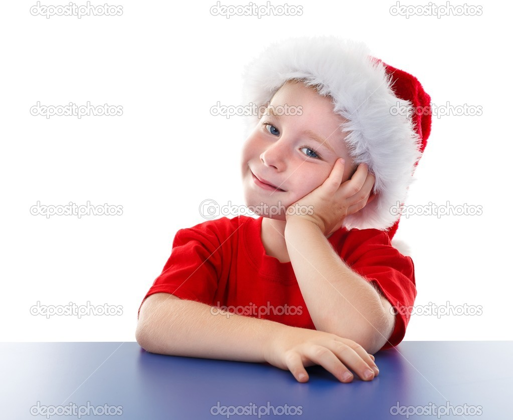 Cute boy sitting at table, wearing Christmas clothes, looking to us — Stock Photo #7026321