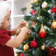 Little boy decorating Christmas tree - Stock Photo