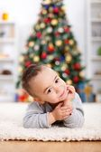 Cute boy laying in front of christmas tree — Stock Photo