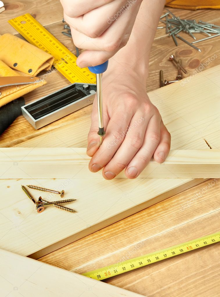 Man's hands screwing bolt into a plank — Stock Photo #6849678