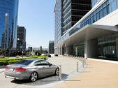 Luxury car near modern building's entrance — Stock Photo
