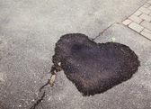 Humedezca la mancha oscura en el asfalto en forma de corazón — Foto de Stock
