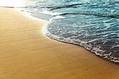 Shiny tropic sea wave on golden beach sand — Stock Photo