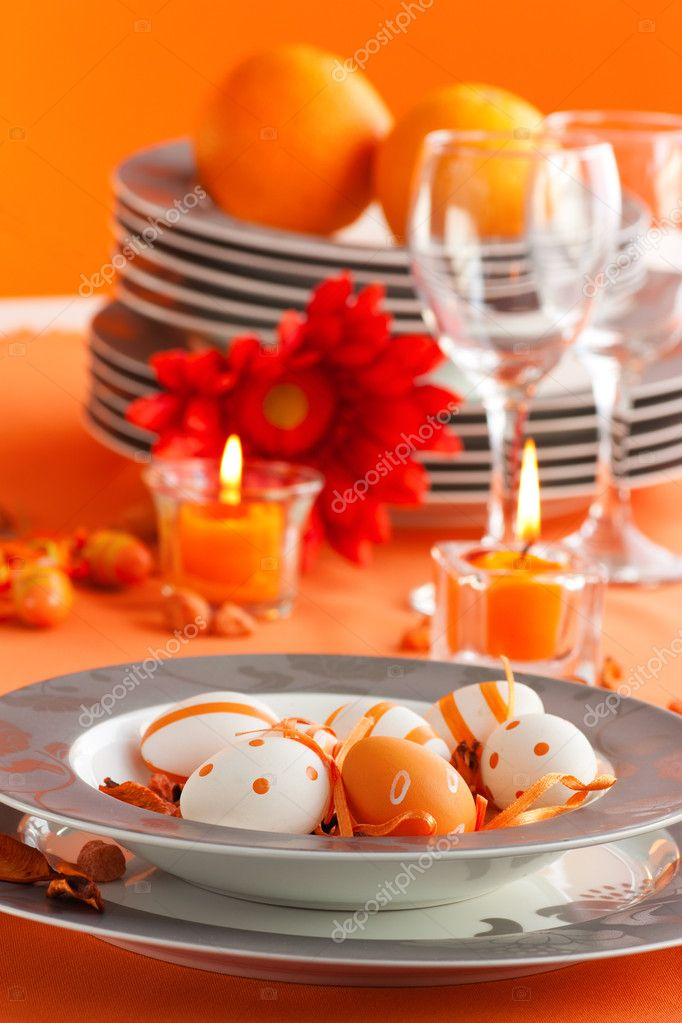 Easter table setting in orange tones with candles and flower. — Lizenzfreies Foto #6993815