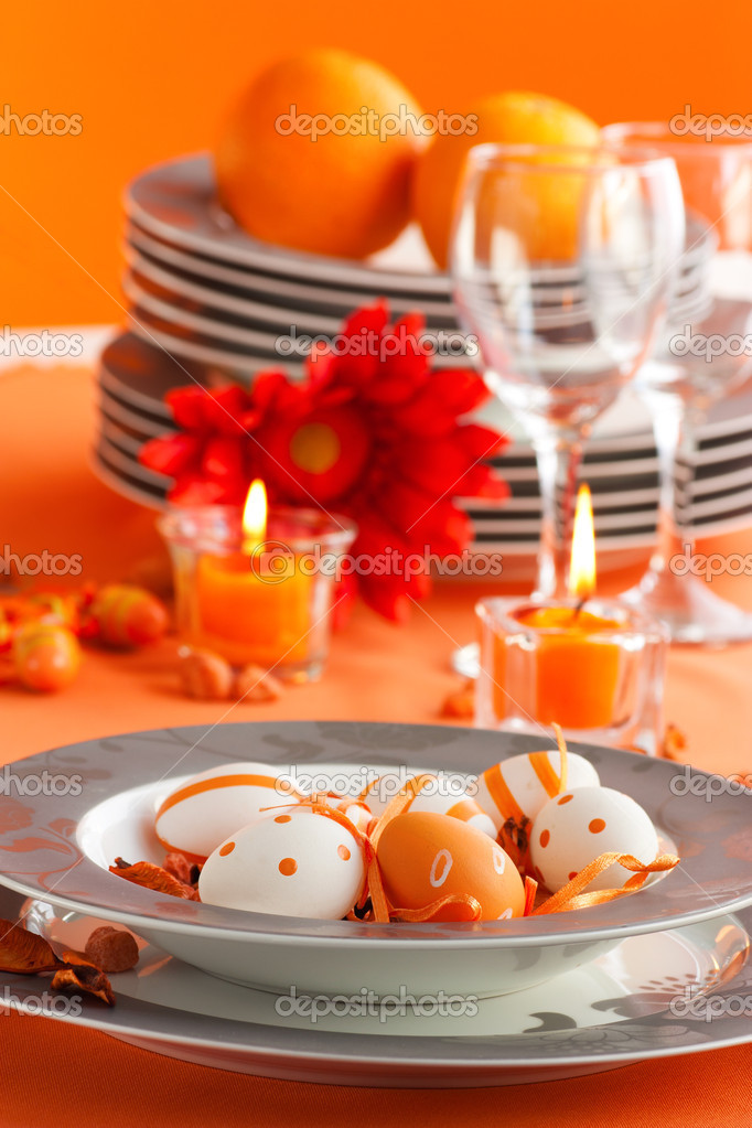 Easter table setting in orange tones with candles and flower.  Foto Stock #6993815