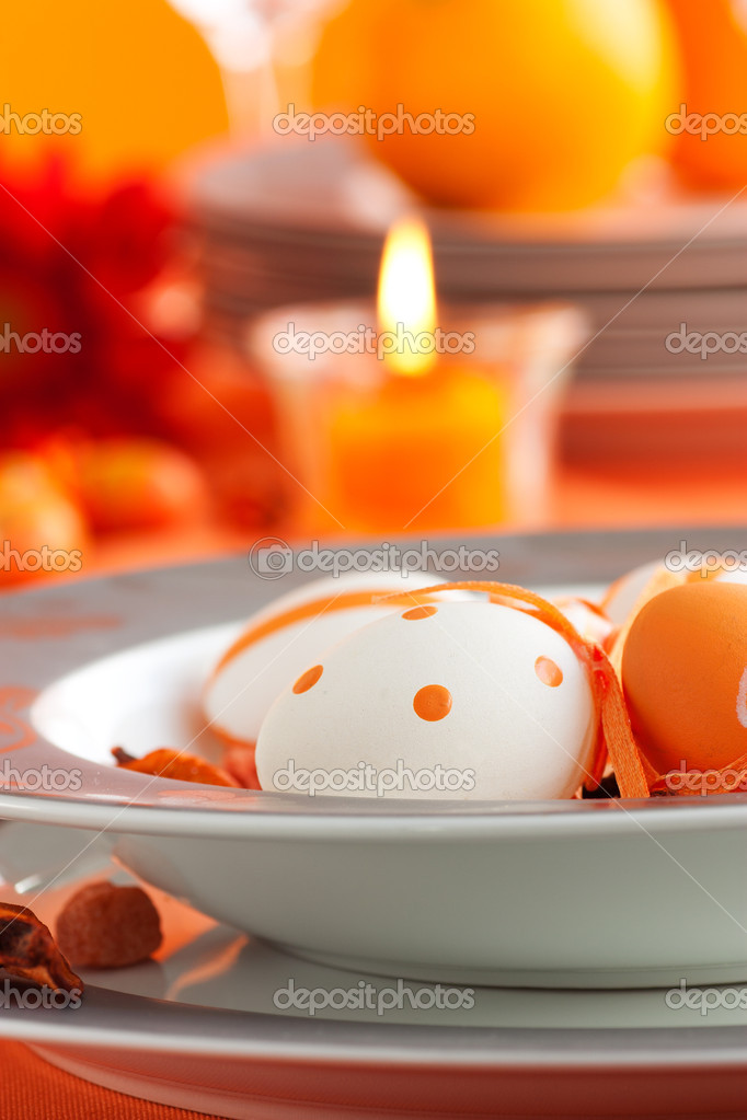 Easter table setting in orange tones with candles and flower.  Stock Photo #6993832
