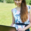 Royalty-Free Stock Photo: Happy girl with PC in the park