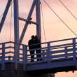 Stock Photo: Couple kissing on a bridge
