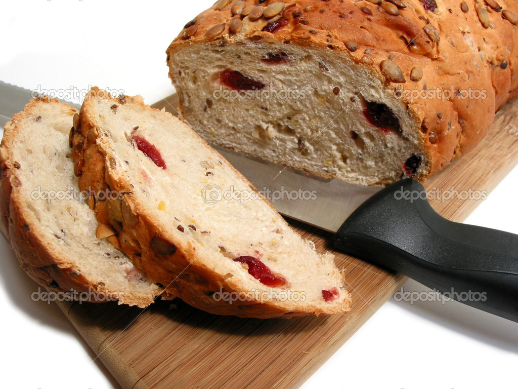 Artisan pumkin seed and cranberry bread on a cutting board with a bread knife, white background — Stock Photo #6980244