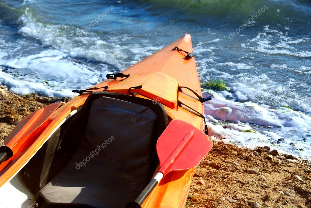 Orange kayak on a sandy shore of a river  Stock Photo #6980615