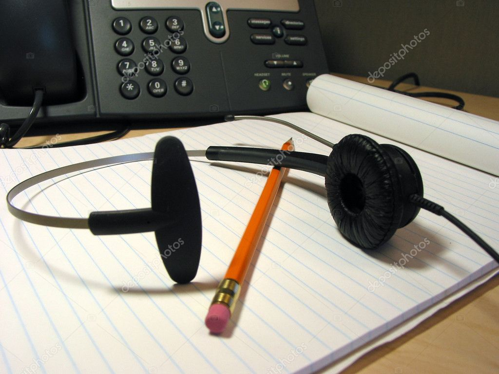 Headset, pencil and notepad on the office desk with IP phone in the background — Stock Photo #7085022