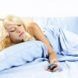 Sad woman with phone in bed — Stock Photo