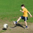 Boy kicking soccer ball — Stock Photo