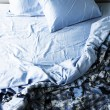 Unmade bed and bedding - Stock Photo