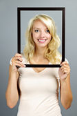 Smiling woman with picture frame — Stock Photo