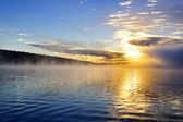 Sunrise on foggy lake — Stock Photo