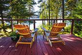 Lesní chata palubou a židle — Stock fotografie