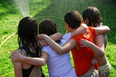 Group of girls and sprinkler — Stock Photo