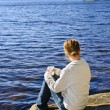 Woman relaxing at beautiful lake - Stock Photo