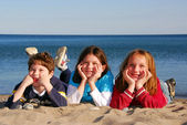 Tre barn på en strand — Stockfoto