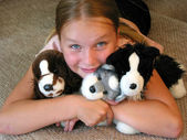 Girl hugging her plush toys — Stock Photo